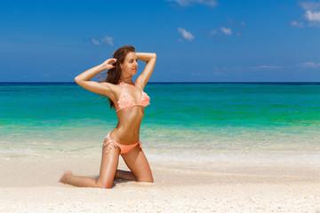 Happy beautiful young girl in bikini on a tropical beach. Blue s
