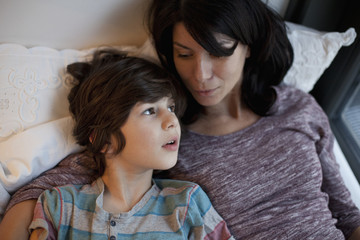 Mother and son lying on bed