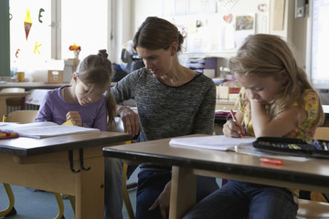 Teacher teaching to girls in classroom