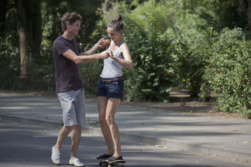 Young man teaching woman to skating