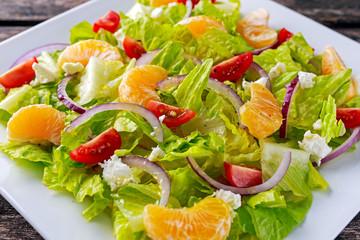 Fresh Mandarin, vegetables salad on wooden table.