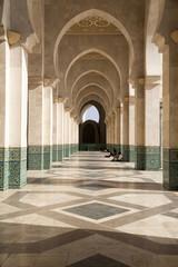 Africa, Morocco, Casablanca. King Hassan II Mosque. Students read in an exterior corridor