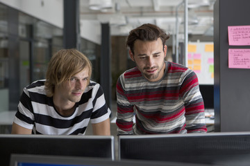 Two men working on computer in office