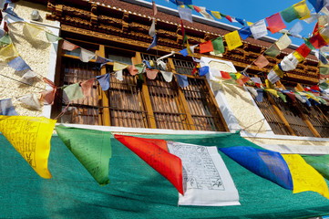 India, Jammu & Kashmir, Ladakh, prayer flags blowing in front of a traditional Ladakh building in downtown Alchi