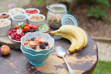 Paleo style breakfast served in the garden: gluten free grain free oat free granola with mixed nuts, and fresh berries and fruits, selective focus