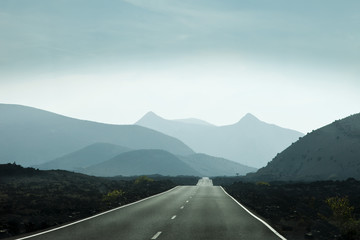 Empty road leading towards mountains in Lanzarote, Canary Islands, Spain