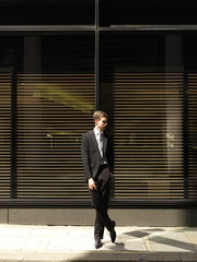 A young businessman standing outside a building, looking away