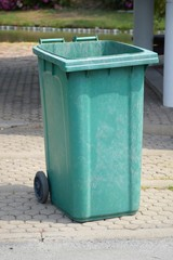 green plastic bin in nature garden