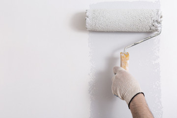 Close up of painter hand painting a wall grey with paint roller