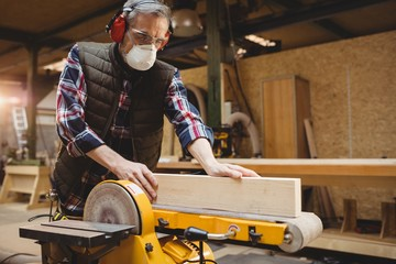 Carpenter sawing a plank of wood