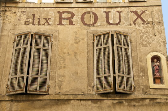 Large painted letters on ancient wall, with statue of the Virgin, and wood shutters, Old Aix, Aix en Provence, Provence, France