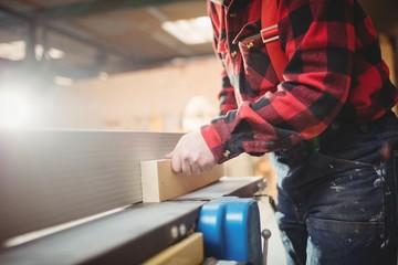 Carpenter sawing a wooden plank in workshop