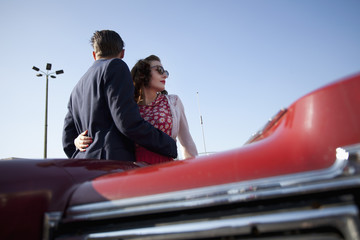 A cool, rockabilly couple with arms around each other by a vintage car