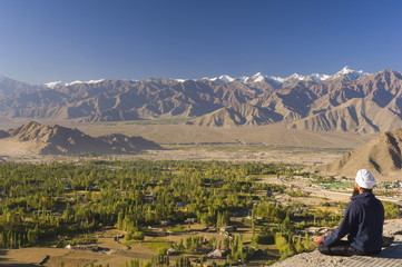Man meditating, with view of Indus Valley and Stok-Kangri massif, Leh, Ladakh, Indian Himalayas, India, Asia