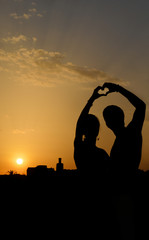 Silhouette of a couple making heart shape