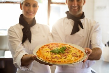 Portrait of two chef presenting a pizza Wall mural
