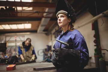 Female welder in protective workwear