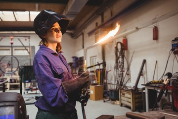 Young woman welder with a flaming torch