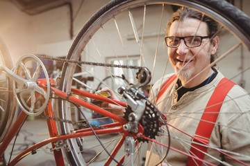 Portrait of a bike mechanic positioned behind a bike wheel