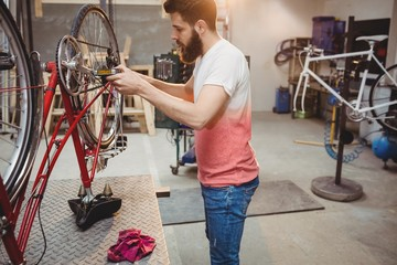 Hipster repairing a bicycle