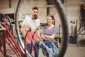 Bicycle repairer colleagues posing behind a bicycle wheel