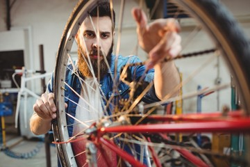 Portrait of a hipster repairing a bicycle wheel