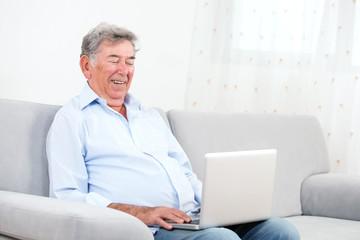 Senior adult smiling while using laptop
