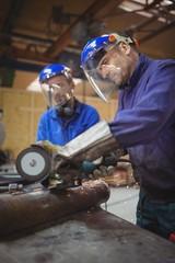 Men cutting metal with circular saw