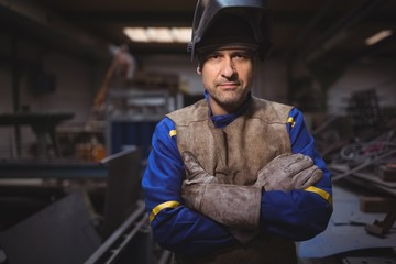 Portrait of welder standing with arms crossed in workshop