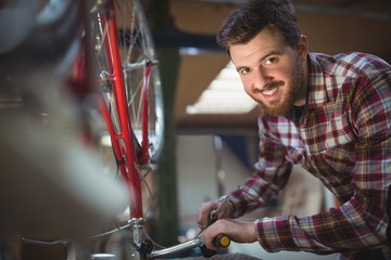 Portrait of smiling mechanic repairing a bicycle