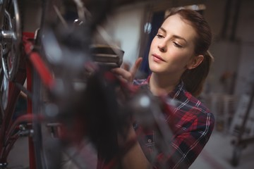 Female mechanic repairing a bicycle