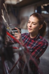 Female mechanic repairing a bicycle