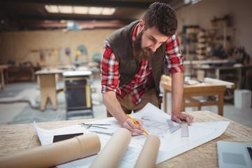 Carpenter working on a blueprint
