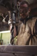Welder working with drilling machine in workshop