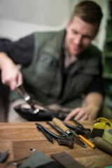 Focus on tools while cobbler is repairing a shoe