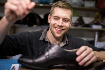 Cobbler putting lace on shoe
