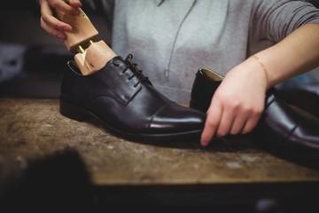 Cobbler placing shoe tree inside the shoes