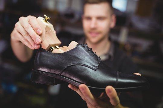 Cobbler placing shoe tree inside the shoe