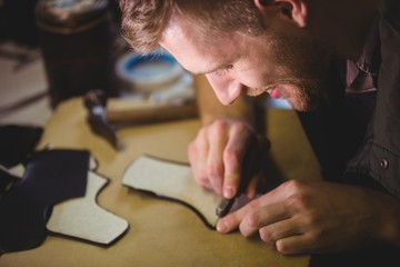 Cobbler using a tool on a piece of material