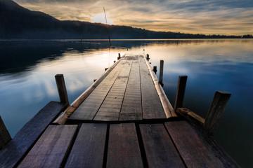 Beautiful wooden jetty and reflection of the nature at Ulun Danu Beratan, BALI, Indonesia