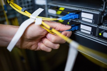 Close-Up of technician plugging patch cable in a rack mounted se