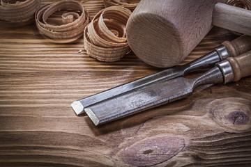 Flat chisels curled shavings wooden hammer on wood board constru