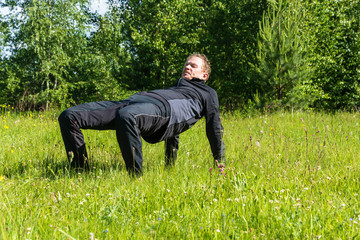 Male performs asanas on the grass.