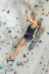 junge Frau beim Sportklettern in der Halle