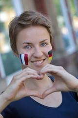 Junge Frau mit Länderflaggen Deutschland und Frankreich macht mit Ihren Händen ein Herz