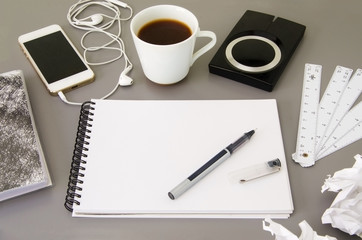 Business workplace.  Top view of grey office desk  with coffee cup, diary, notepad, pen, memory disk, smartphone and earphone.