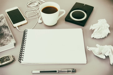 Business workplace.  Top view of grey office desk  with coffee cup, diary, notepad, pen, memory disk, smartphone and earphone. Copy space.