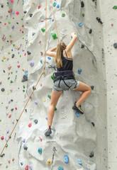 Frau beim Klettern einer Route an der Kletterwand