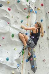 junge Frau in der Kletterhalle