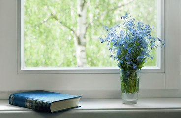 Book and bouquet of forget-me-nots on the window